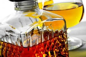 closeup of a vintage glass liquor bottle and some cognac glasses with liquor